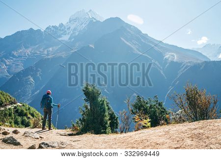 Young Hiker Backpacker Man Using Trekking Poles Enjoying The Thamserku 6608m Mountain With Flying Re
