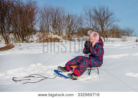 Cute Girl With A Red Cup Sits In A Sleigh In The Snow. The Child Warms Himself With Hot Tea.