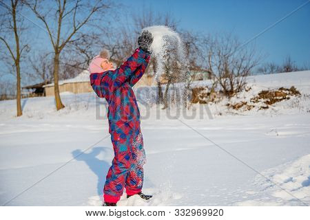 Cheerful Girl Throws Snow On A Sunny Winter Day. Active Games With Snow. The Winter Vacation.
