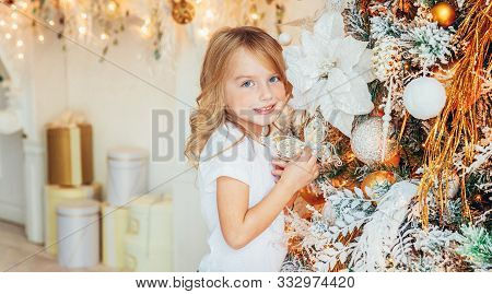 Little Girl Decorating Christmas Tree On Christmas Eve At Home. Young Kid In Light Room With Winter