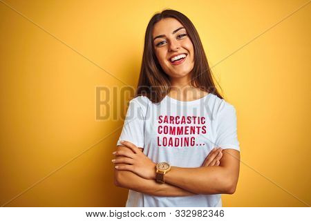 Beautiful woman wearing fanny t-shirt with irony comments over isolated yellow background happy face smiling with crossed arms looking at the camera. Positive person.