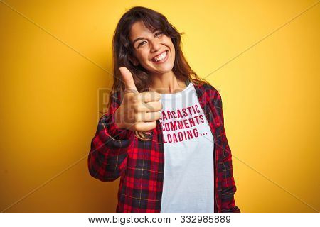 Beautiful woman wearing funny t-shirt with irony comments over isolated yellow background happy with big smile doing ok sign, thumb up with fingers, excellent sign