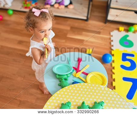 Beautiful caucasian infant playing with toys at colorful playroom. Happy and playful cooking in fake kitchen at kindergarten.