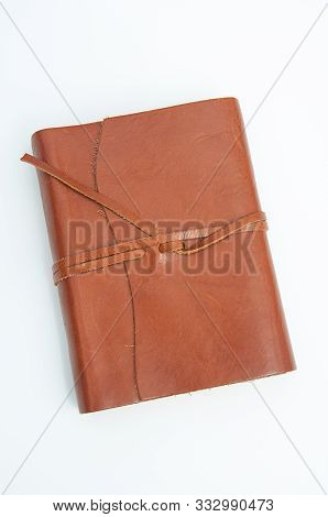 Brown Leather Journal Isolated On A Light Background In Vertical Orientation.  Leather Straps Tie Th