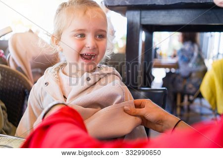 Beautiful toddler child girl sitting on baby highchair  and woman laughing