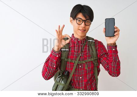 Chinese hiker man wearing canteen holding smartphone over isolated white background doing ok sign with fingers, excellent symbol