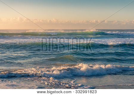 Ocean Seascape With Beautiful Sunlit Waves At Sunrise. Summer Beach Vacation Surf Background