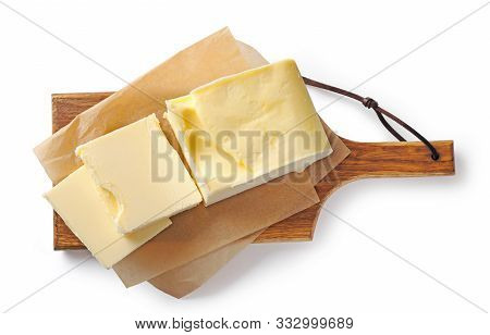 Pieces Of Butter On Wooden Cutting Board Isolated On White Background, Top View