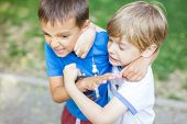 Two boys fighting outdoors. Friends wrestling in summer park. Siblings rivalry. poster