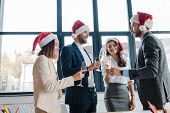 happy multicultural businesswomen and businessmen in santa hats holding champagne glasses in office poster