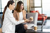 Two asian businesswomen discussing with the partner business with technology laptop during coffee break in modern office or coworking space, coffee break, relaxing and talking, partner and colleague poster