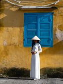Young Vietnamese woman wearing a white ao dai or traditional garment with a straw hat walking in front of a large turquoise door with grate. poster