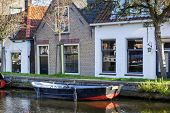 Nostalgia quayside with an old boat and historical houses in Schipluiden in the Netherlands poster