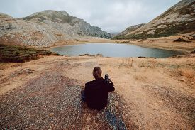 Stock Aerial Photo Of A Photographer Girl From Behind Sitting In Front Of A Lake Surrounded By Mount