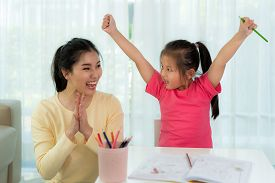 Happy Successful Asian Kindergarten Student And Her Mother Hands Raised Up To Celebrate The Successf