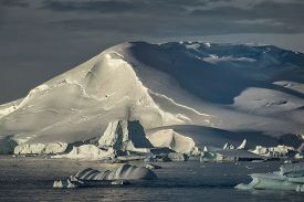 Sunlit icy mountain glacier and icebergs along the Antarctic Peninsula