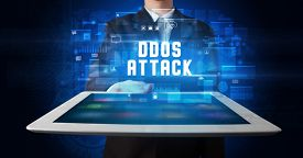 Young business person working on tablet and shows the digital sign: DDOS ATTACK