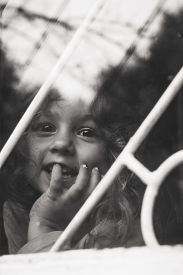 Black And White Portrait Of Happy Little Girl Looks Through Window With Lattice