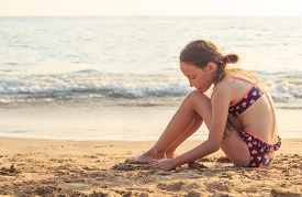 Portrait Of Beautiful Teen Girl Sitting And  Playing With Sand By The Sea Waves.  Summer Sunny Day,