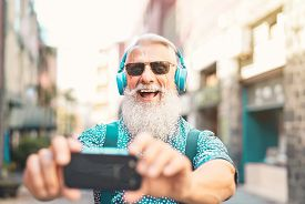 Senior Bearded Man Taking Selfie With Mobile Phone While Listening Favorite Playlist With Headphones