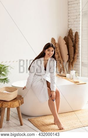 Vertical Shot Of Cheerful Woman Touching Smooth Legs In Bathroom