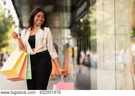 Black Woman With Shopping Bags Looking At Mall Window