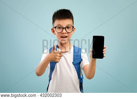 Educational App. Excited Asian Schoolboy Pointing At Smartphone With Blank Black Screen