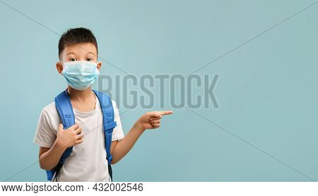 Check This. Asian Schoolboy Wearing Medical Face Mask And Backpack Pointing Aside
