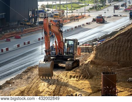 A Crawler Excavator Works At A Construction Site Next To The Road. Urban Construction Background Wit