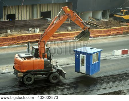 A Wheeled Excavator Transports A Booth. The Excavator Is Driving Through The Construction Site. In T