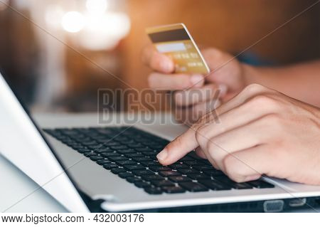 Businessman Hand Holding Credit Card With Using Laptop For Online Shopping While Making Orders At Ho