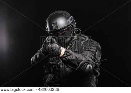 A Man In Glasses, A Helmet And A Bulletproof Vest Aims At The Camera, Photo On A Black Background.