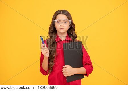 Serious Teenager Girl In Protective Glasses Making Notes In Folder With Documents, Study