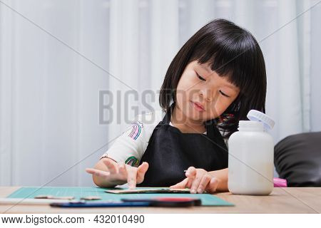 Pupil Kid Girl With Paper And Glue Making Cardboard Box Houses. Homework School Child. Young Female