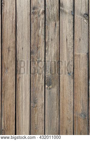 A Wooden Fence With A Pronounced Knotty Texture, A Natural Background Of Unpainted Wood With A Rough