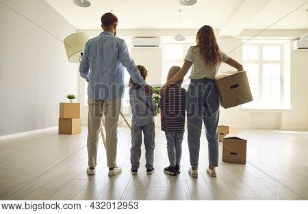 Happy Couple With Children Standing Together In Their Own New House With Cardboard Boxes.