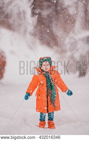 A Happy Girl In A Red Jacket And Ukrainian National Kerchief Walks In A Snowy Yard.