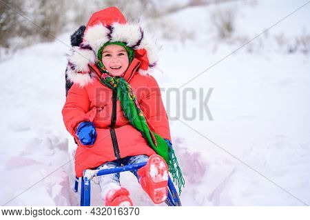 Little Girl Sitting On A Sleigh On A Snowy Winter Day, Warm Winter Clothes, A Red Jacket And A Green