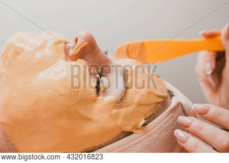 Using A Gold Mask In Cosmetology, A Woman At A Beautician Applying A Gold Mask On Her Face.