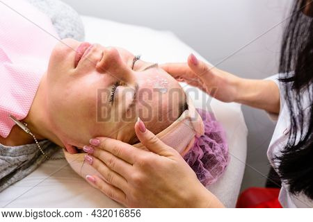 Happy And Relaxed Woman On Cosmetology Procedures, Massage And Applying Face Cream.