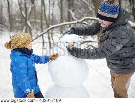 Little Boy With His Father Building Snowman In Snowy Park. Active Outdoors Leisure With Family With