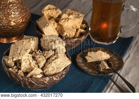 Sunflower And Peanut Halva Are In A Ceramic Bowl On A Blue Napkin, Behind A Copper Vase And A Cup Of