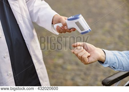 Close Up Of Medical Infrared Thermometer In A Hand Of Doctor Measuring The Temperature Of Male Handi