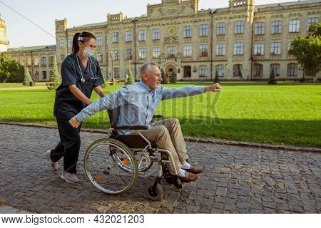 Full Length Shot Of Cheerul Aged Man, Recovering Patient Making Superman Gesture On A Walk With Cari
