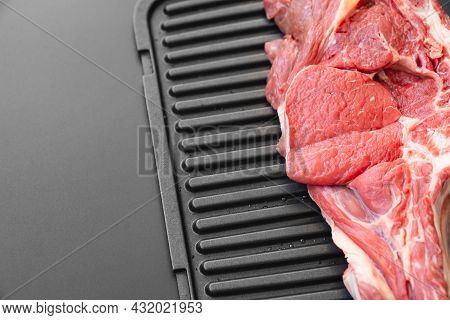 Piece Of Beef On Bone On Black Grill Pan .natural And Eco-friendly Farm Products