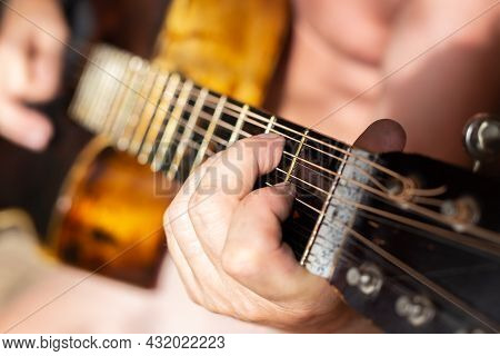 A Man Plays A Twelve-string Acoustic Guitar. Hobbies And Entertainment.