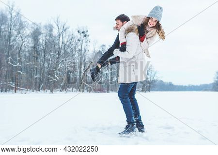 Young Happy Couple Lies In The Snow, Throws Snow And Plays In The Winter Park. Man And Woman Have Fu