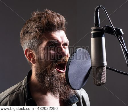 Closeup Portrait Of Man With Microphone Singing Song. Musician In Music Hall. Funny Guy Singing.