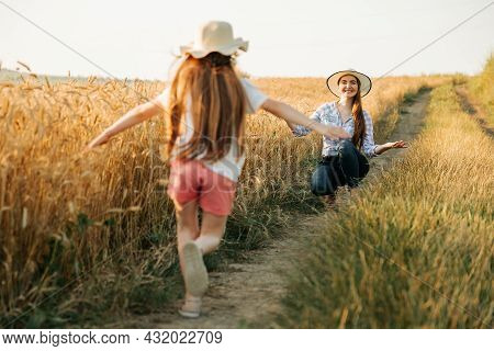 Happy Little Girl With Hat On Her Head Runs To Her Mother Next To A Wheat Field, A Family Of Farmers