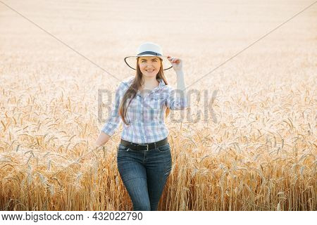 Portrait Of A Smiling Beautiful And Attractive Farmer Woman Wearing Hat Is In The Field With Yellow